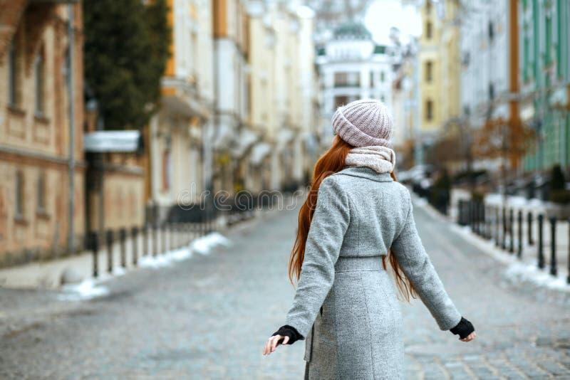 Ładna czerwieni głowy kobieta jest ubranym zimy nakrętkę pozuje przy żakiet i obraz stock