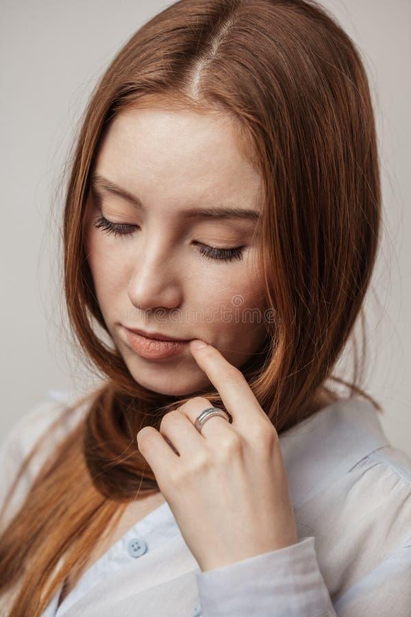 Ładna czerwona z włosami kobieta patrzeje kamerę z th z niebieskimi oczami zdjęcie stock