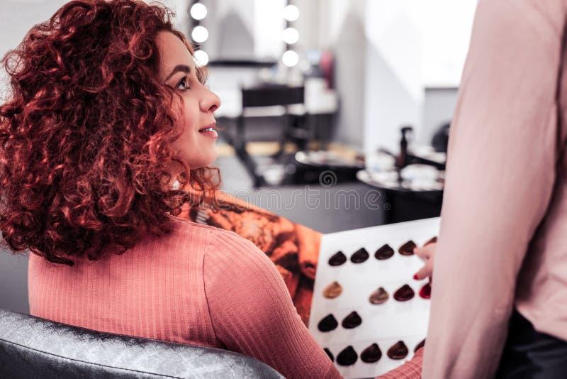 Ładna czerwona z włosami kobieta słucha jej fryzjer obraz stock