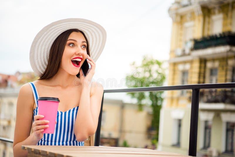 Ładna dama mówi nad telefonem słucha wielkiego wiadomości obsiadanie w wygodnym ulicznym cukiernianym odzieży słońca kapeluszu i  obrazy stock