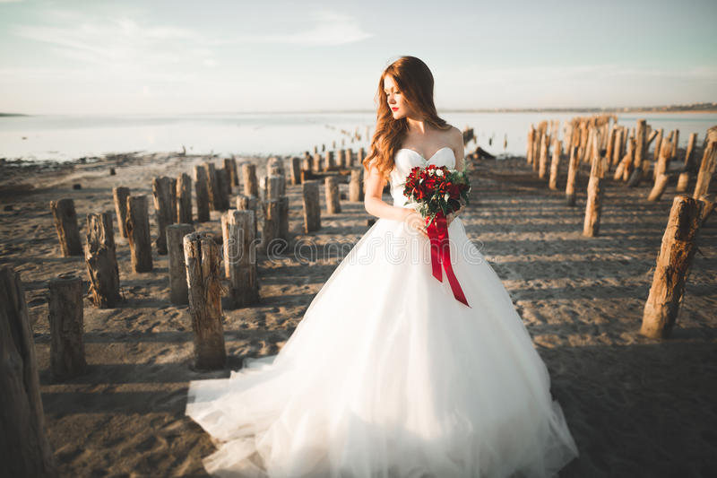 Ładna dama, panna młoda pozuje w ślubnej sukni blisko morza na zmierzchu zdjęcia royalty free