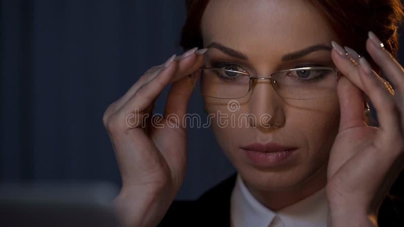 Ładna dama stawia szkła dalej, pracujący z laptopem, zakończenie w górę żeńskiej twarzy zdjęcia royalty free