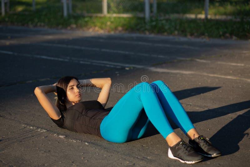 Ładna dysponowana kobieta robi abs chrupnięciom przy stadium zdjęcie stock