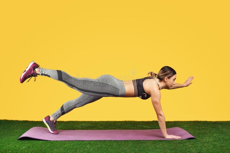 Ładna dysponowana młoda kobieta ćwiczy na sprawności fizycznych purpur macie na zielonej trawie nad żółtym tłem fotografia royalty free