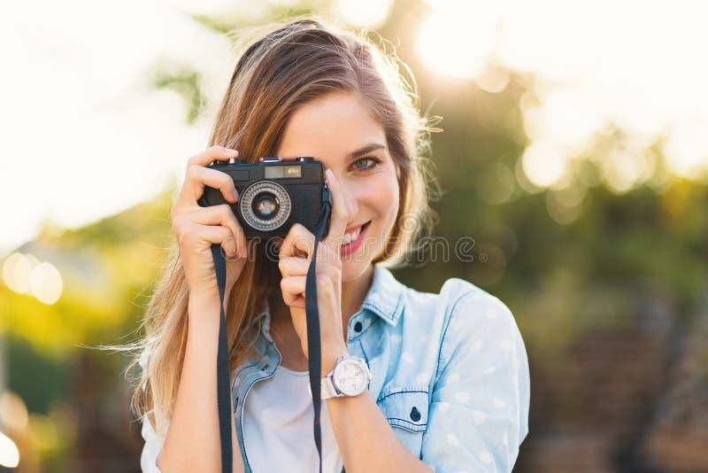 Ładna dziewczyna bierze fotografie z rocznik kamerą na słonecznym dniu zdjęcie stock