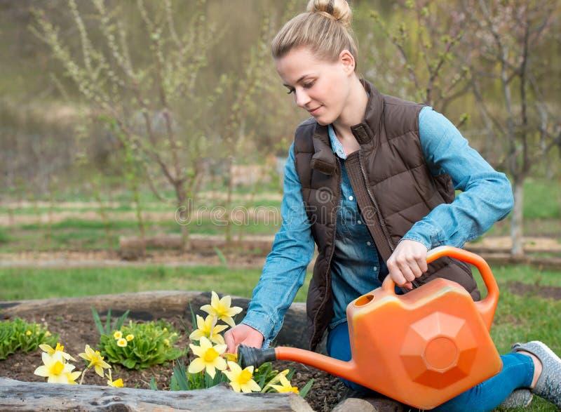 Ładna dziewczyna bierze opiekę ogród Nawadniać kwitnie od waterin fotografia stock