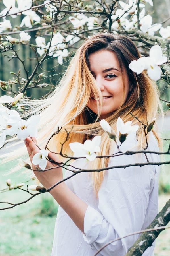 Ładna dziewczyna cieszy się kwitnących magnoliowych drzewa, ona długie włosy w m zdjęcia royalty free