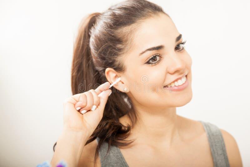 Ładna dziewczyna czyści jej ucho w łazience fotografia royalty free
