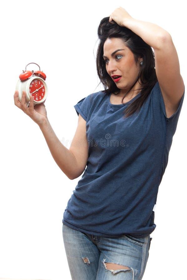 Ładna dziewczyna okaleczał spojrzenia przy zegarem, studio, odizolowywający zdjęcia stock