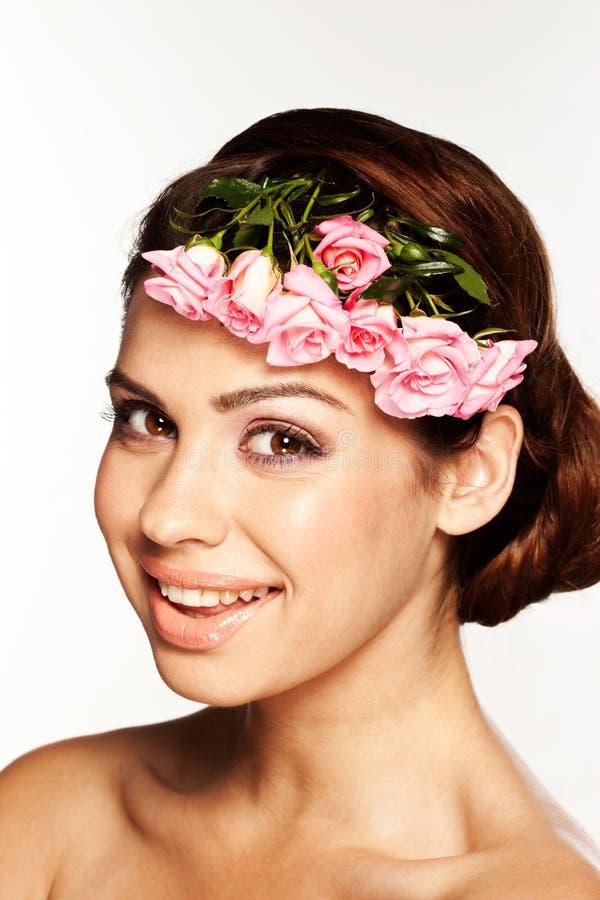 Ładna dziewczyna ono uśmiecha się z kwiatami zdjęcia stock
