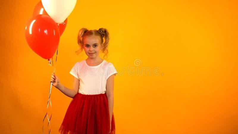 Ładna dziewczyna patrzeje kamera z lotniczymi balonami, świętuje przyjęcia urodzinowego obraz royalty free