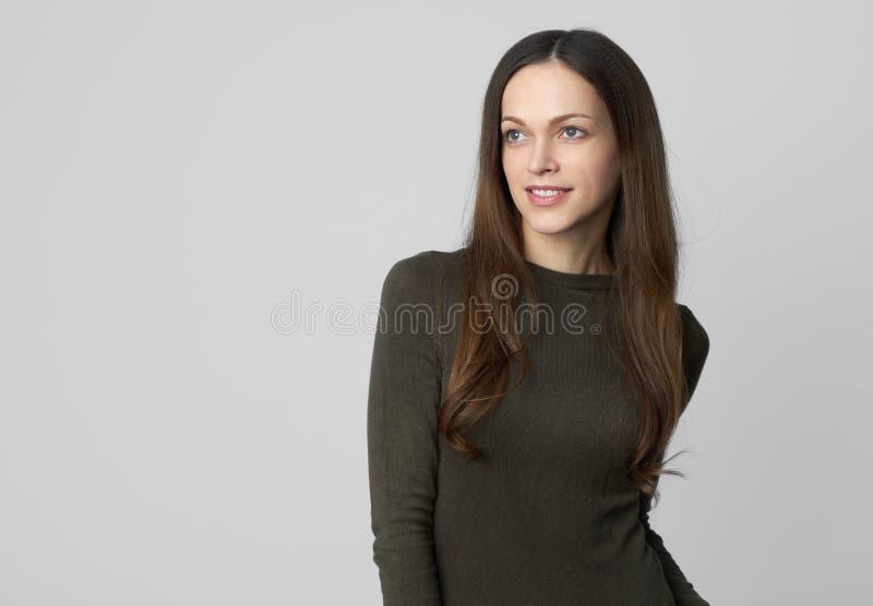 Ładna dziewczyna patrzeje oddalony i uśmiechnięty w przypadkowych ubraniach odosobniony obrazy stock