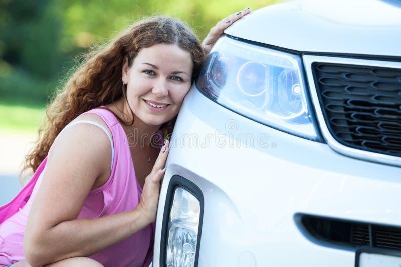 Ładna dziewczyna siedzi jej policzek przeciw zderzakowi samochód zdjęcia royalty free