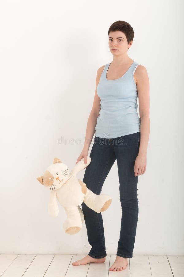 Ładna dziewczyna stoi nad białym tłem bosym z mokiet zabawki kotem w jej ręce i spęczeniu, patrzejący poważnie folował zdjęcie royalty free
