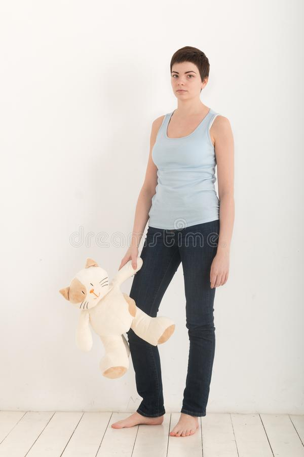 Ładna dziewczyna stoi nad białym tłem bosym z mokiet zabawki kotem w jej ręce i spęczeniu, patrzejący poważnie folował obrazy stock