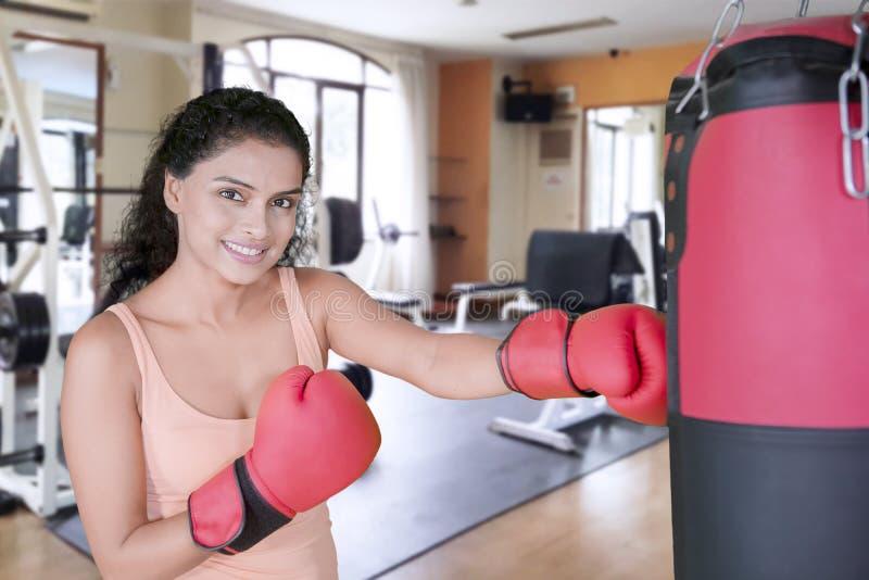 Ładna dziewczyna uderza pięścią bokserskiego worek w gym centrum obraz stock