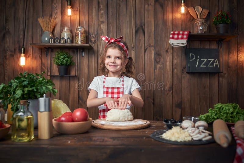 Ładna dziewczyna ugniata chlebowego ciasto dla pizzy w w kratkę fartuchu zdjęcie stock