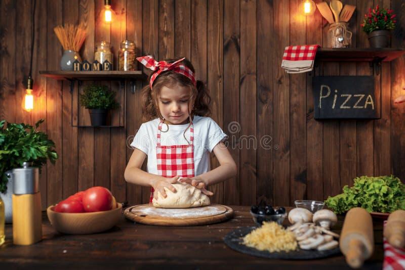 Ładna dziewczyna ugniata chlebowego ciasto dla pizzy w w kratkę fartuchu zdjęcia royalty free