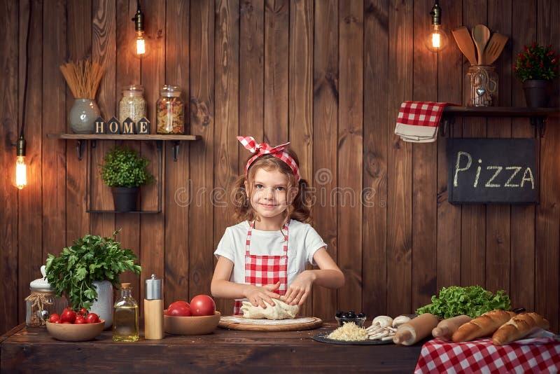 Ładna dziewczyna ugniata chlebowego ciasto dla pizzy w w kratkę fartuchu fotografia royalty free
