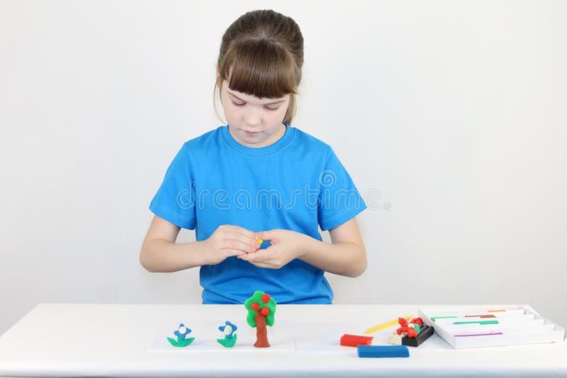 Ładna dziewczyna w błękitnych foremkach od plasteliny na bielu stole zdjęcie stock