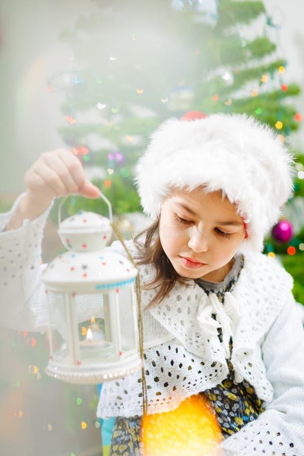 Ładna dziewczyna w Bożenarodzeniowym kapeluszu z candlestick w jej rękach, drzewo zdjęcie stock