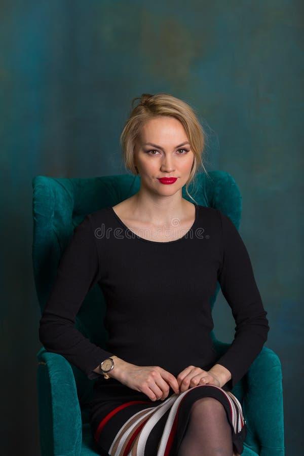Ładna dziewczyna w czerni sukni obsiadaniu w krześle i patrzeć kamerę zdjęcia stock