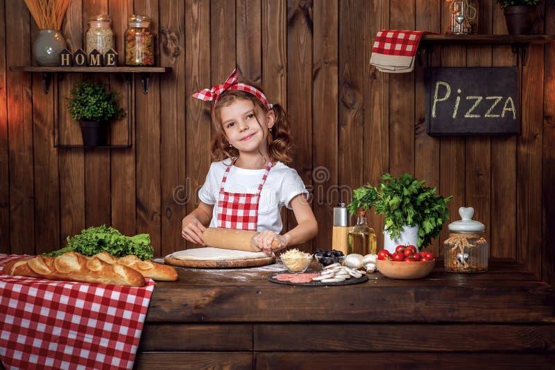 Ładna dziewczyna w w kratkę fartuchu tocznym za cieście dla pizzy zdjęcie royalty free