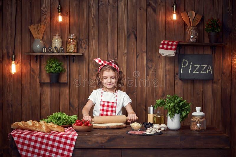 Ładna dziewczyna w w kratkę fartuchu tocznym za cieście dla pizzy obrazy royalty free