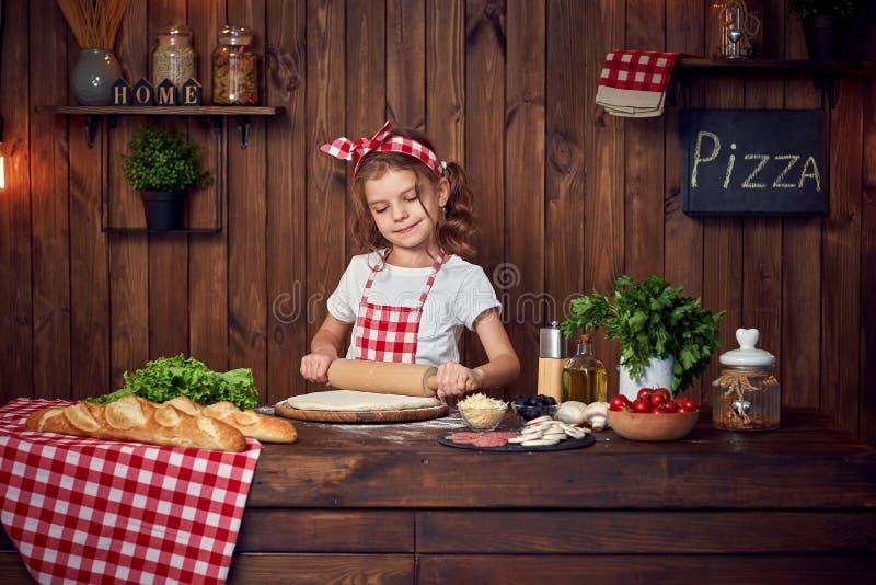 Ładna dziewczyna w w kratkę fartuchu tocznym za cieście dla pizzy zdjęcie stock