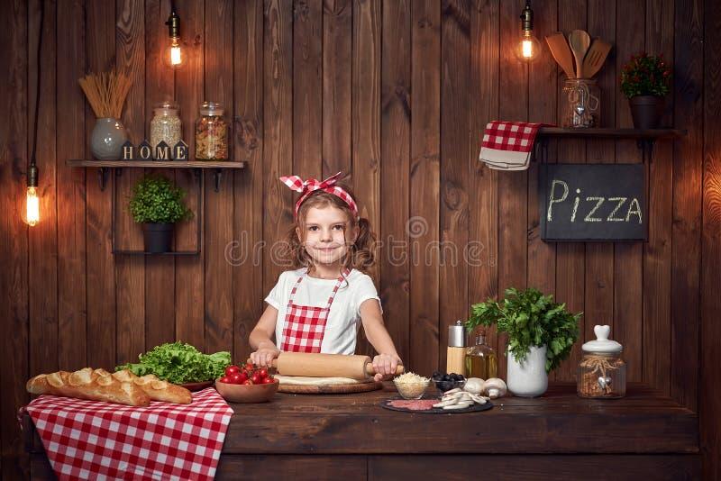 Ładna dziewczyna w w kratkę fartuchu tocznym za cieście dla pizzy zdjęcia stock