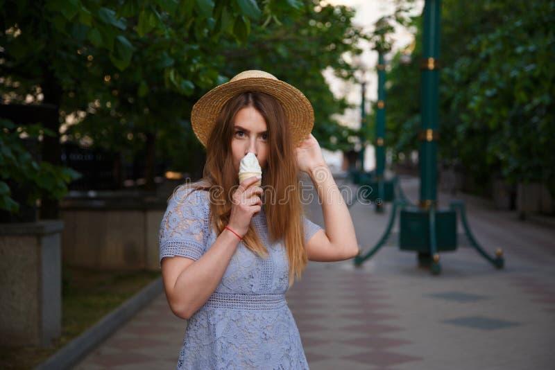 Ładna dziewczyna w lato kapeluszu je lody plenerowego obraz stock