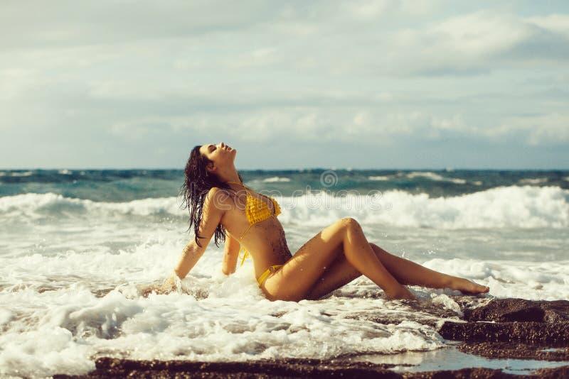 Ładna dziewczyna w seksownym żółtym swimsuit obsiadaniu na skalistej plaży zdjęcia stock