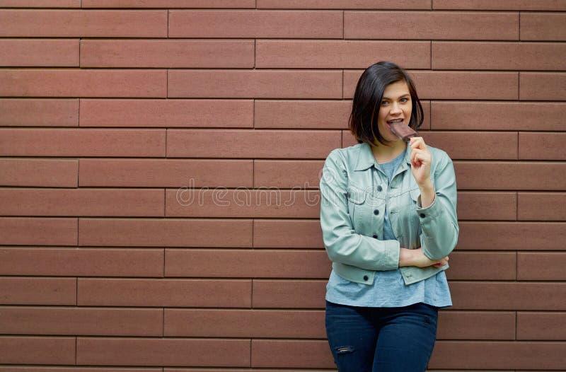 Ładna dziewczyna w szarej skórzanej kurtce kosztuje lody w choco zdjęcie stock