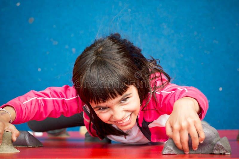 Ładna dziewczyna wspina się ścianę w boisku zdjęcia stock