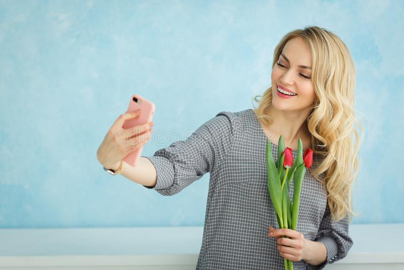 Ładna dziewczyna z bukietem tulipany robi selfie na telefonie obrazy royalty free