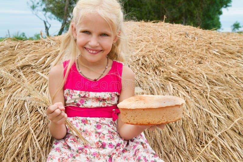Ładna dziewczyna z chlebowym obsiadaniem na haystack zdjęcia stock