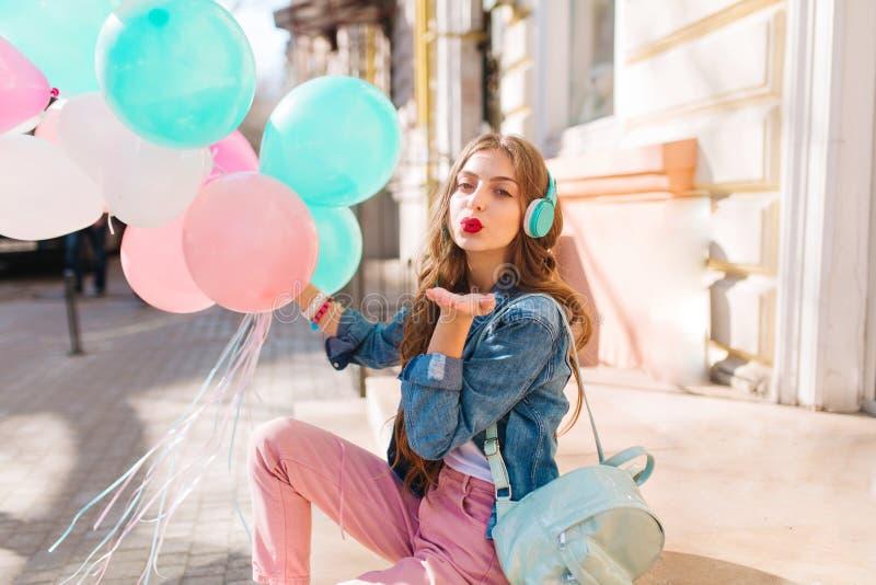 Ładna dziewczyna z długie włosy jest ubranym różowymi spodniami wysyła buziaka podczas gdy czekać na partyjnego obsiadanie na uli zdjęcie stock