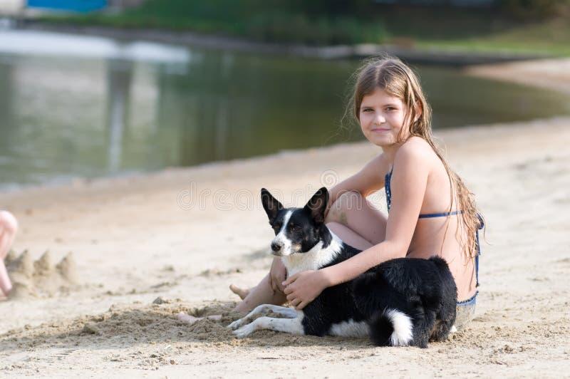 Ładna dziewczyna z jej psem na plaży obrazy stock