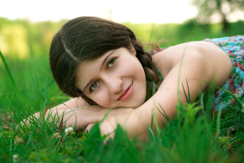 Ładna dziewczyna z pięknym uśmiechem pozuje na gr obraz stock