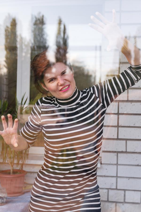 Ładna dziewczyna za okno Jest przyglądająca przez szkła zdjęcie stock