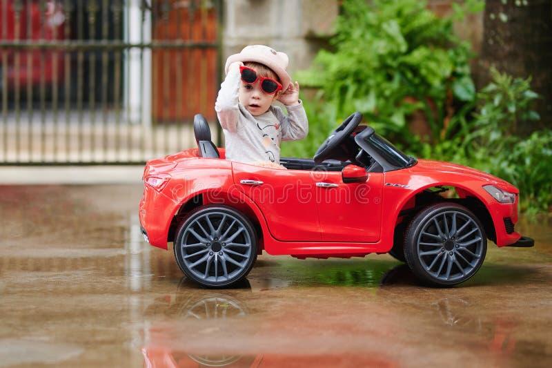 Ładna dziewczynka w czerwieni zabawki samochodzie fotografia royalty free