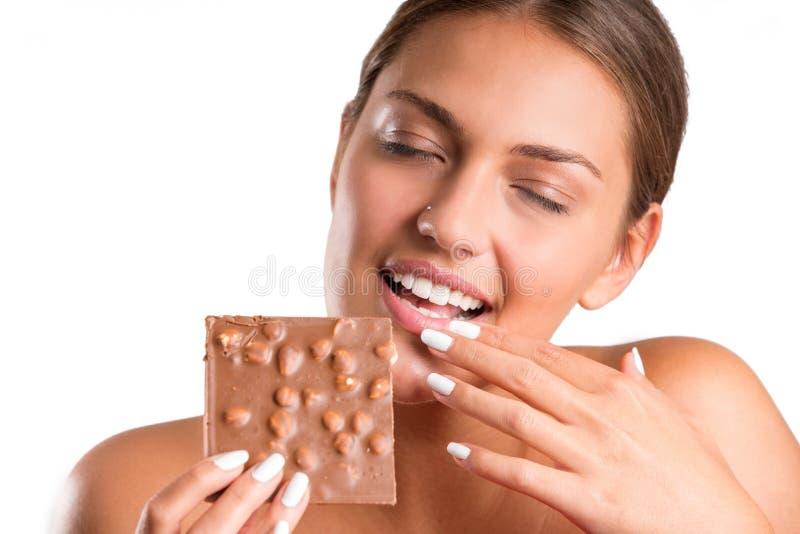 Ładna dziewczyny łasowania czekolada odosobniony obraz stock
