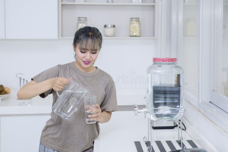 Ładna dziewczyny dolewania świeża woda w domu zdjęcie stock