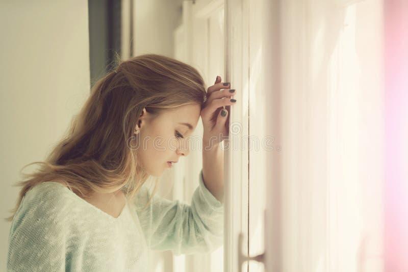 Ładna dziewczyny pozycja przy okno fotografia royalty free