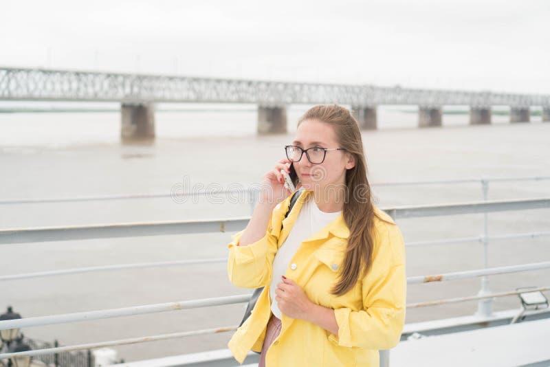 Ładna Europejska kobieta w żółtej drelichowej kurtce poważnie opowiada na telefonie przeciw tłu rzeka Portret zdjęcie royalty free