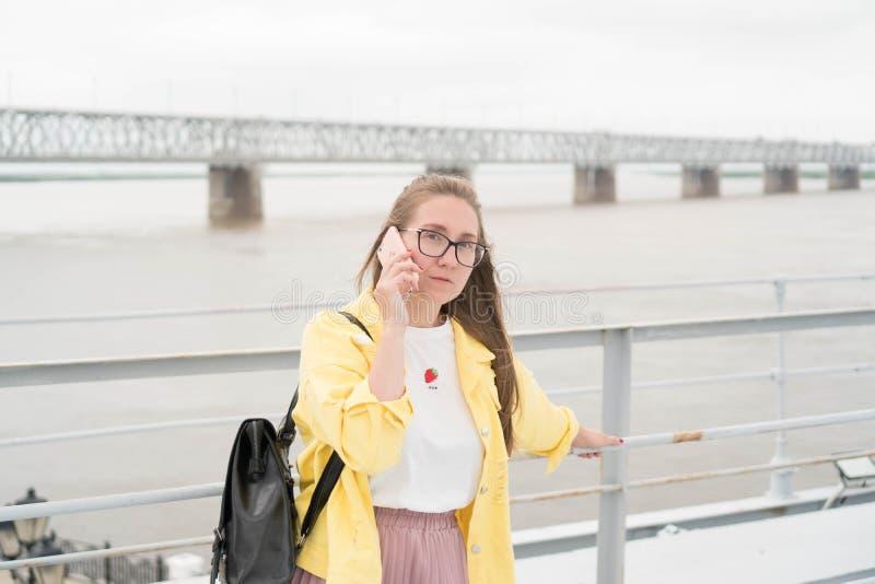 Ładna Europejska kobieta w żółtej drelichowej kurtce poważnie opowiada na telefonie przeciw tłu rzeka Portret obraz stock