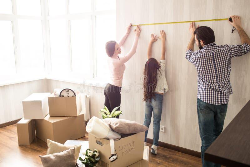 Ładna i pracowita rodzina pracuje wpólnie Mężczyzna i kobieta mierzymy długość ściana podczas gdy ich zdjęcia royalty free