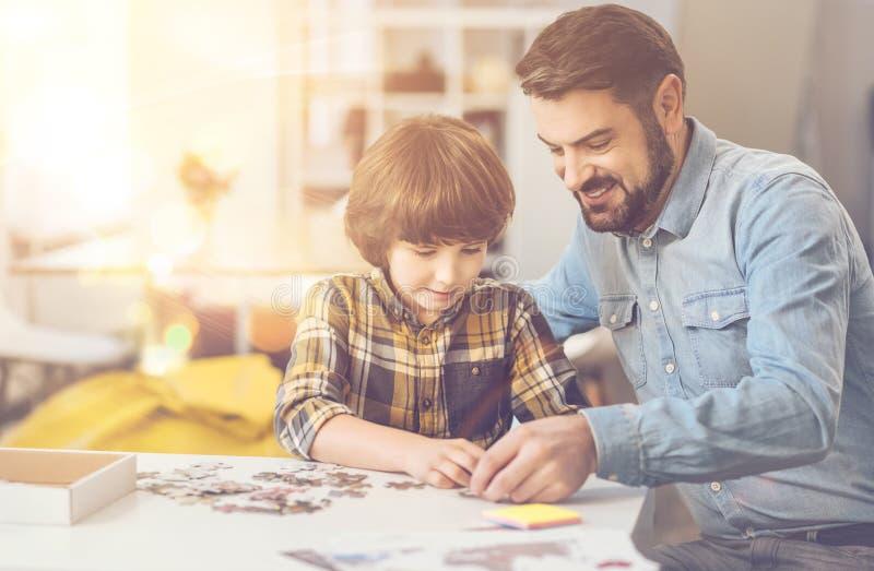 Ładna inteligentna chłopiec robi wyrzynarki łamigłówce z jego ojcem zdjęcie royalty free