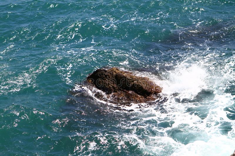 Ładna kamienista jaskrawa błękitna morze plaża z ampuła kamieniami na letnim dniu, fotografia natura obraz stock