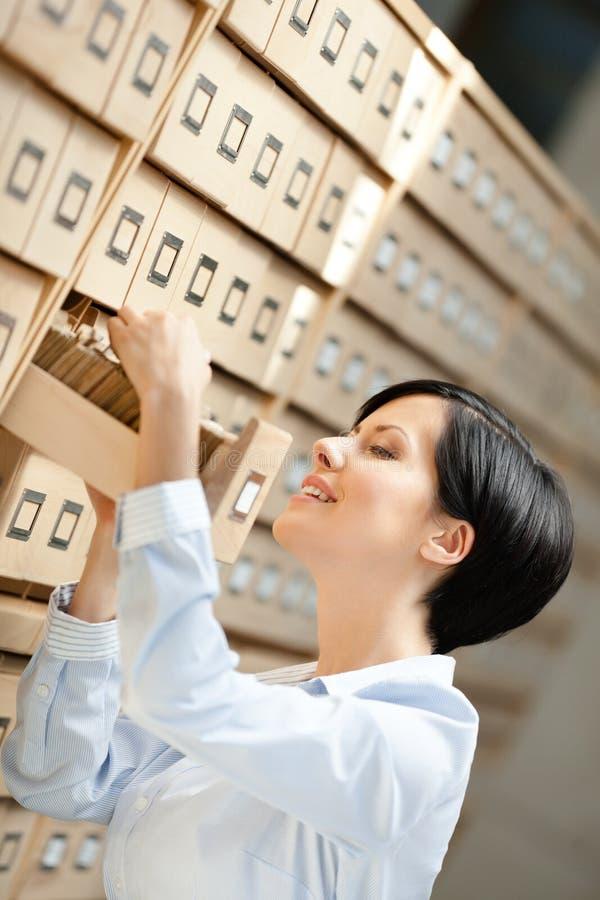 Ładna kobieta bada katalog w karcianym katalogu obrazy stock